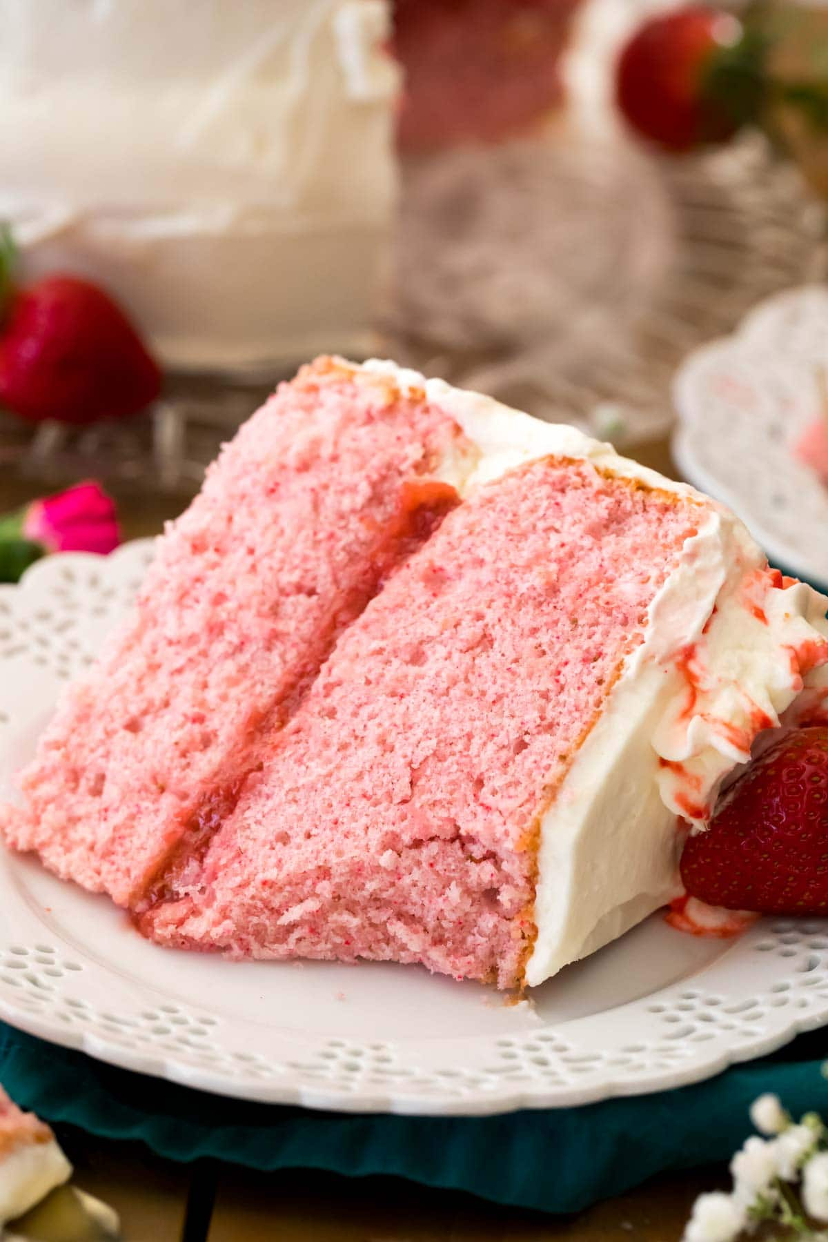 strawberry cake made from scratch on white plate. forkful missing to show soft and fluffy texture