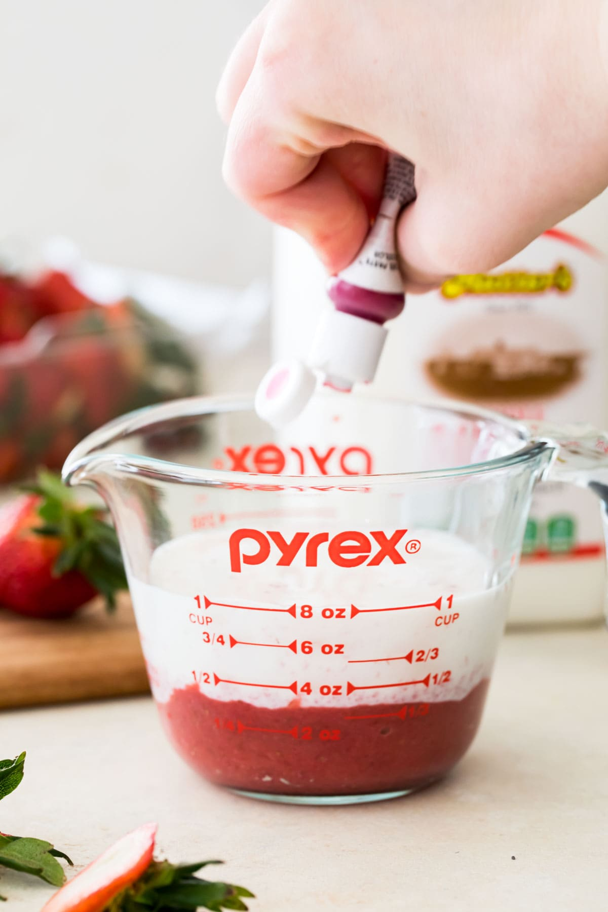 combining milk, strawberry puree, and food coloring in measuring cup