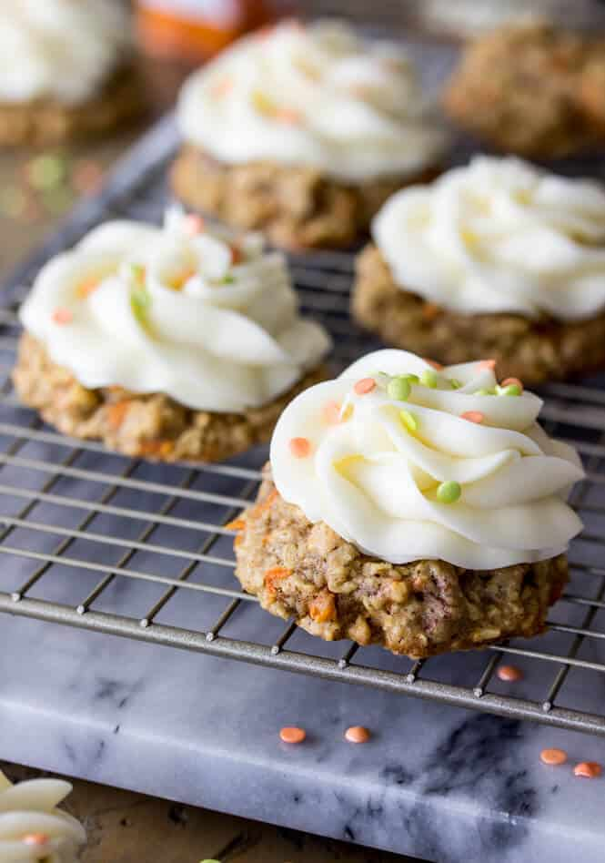 Carrot cake cookies on cooling rack, topped with cream cheese frosting