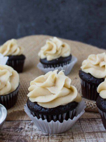 mini dark chocolate cupcakes with caramel frosting in cupcake wrapper
