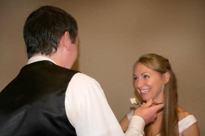 groom feeding bride slice of cake
