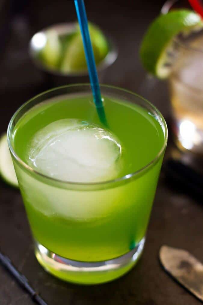 green drink with round ice cube in glass