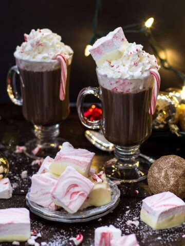 Peppermint marshmallow candy squares with glass mugs of hot chocolate in the background