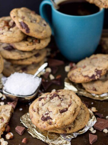 Browned butter and hazelnut chocolate chip cookies scattered around a mug of coffee