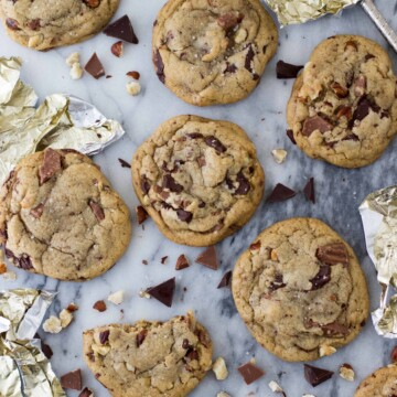 Overhead of browned butter and hazelnut chocolate chip cookies on a marble surface