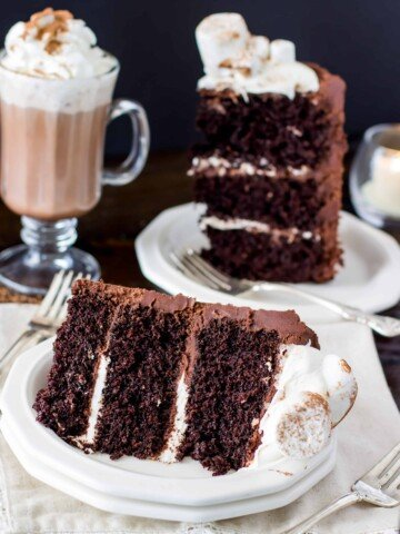 Slice of hot chocolate cake topped with marshmallows with a mug of hot chocolate in the background