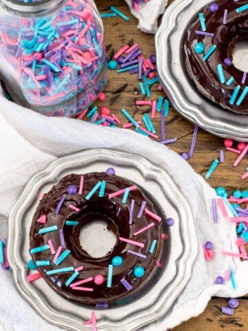 Overhead of baked chocolate donuts with chocolate glaze and sprinkles
