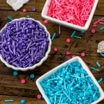 Three bowls: one filled with blue sprinkles, one with pink sprinkles, one with purple sprinkles