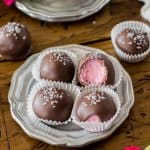Chocolate covered strawberry buttercream candies on a silver plate