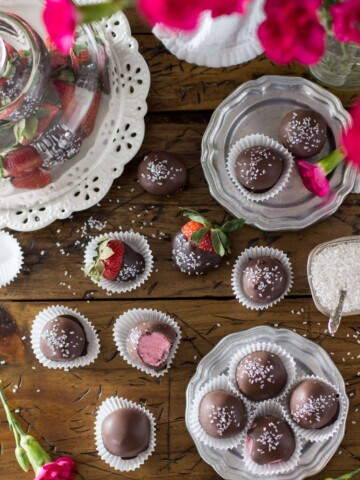 Overhead of strawberry buttercream candies arranged on a silver plate and wood surface, surrounded by chocolate covered strawberries