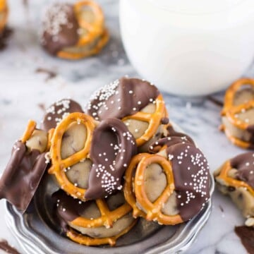 Chocolate covered pretzel bites stuffed with cookie dough, piled on to a silver plate