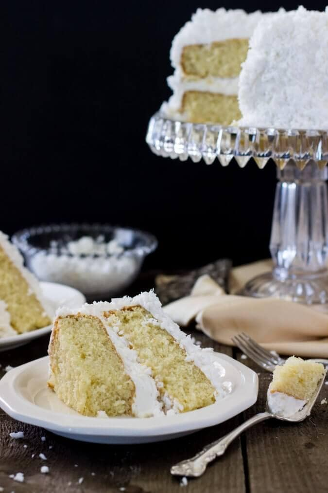 Slice of cake on a white plate with the rest of the cake on a glass cake stand in the background