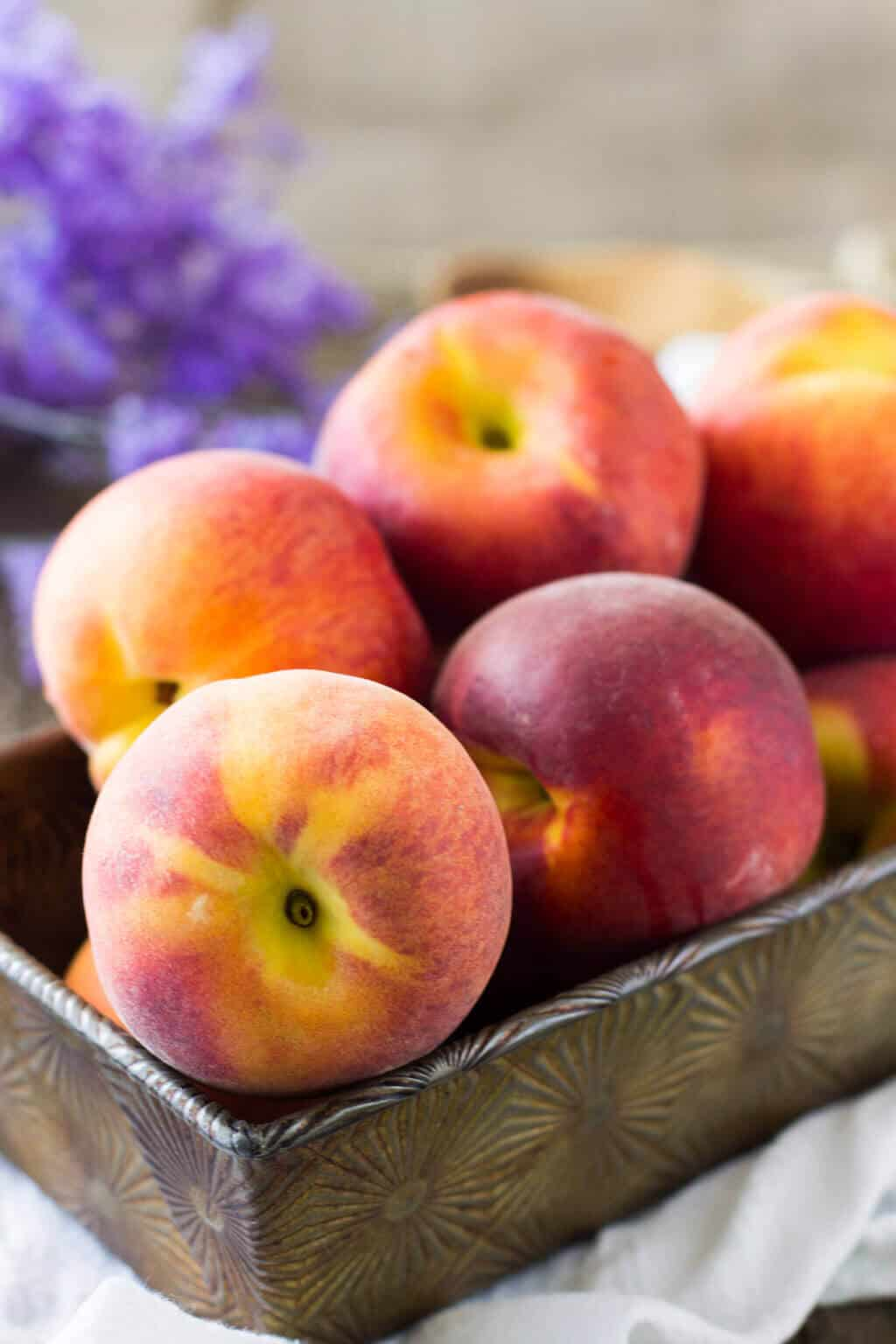 Peaches stacked in a metal dish