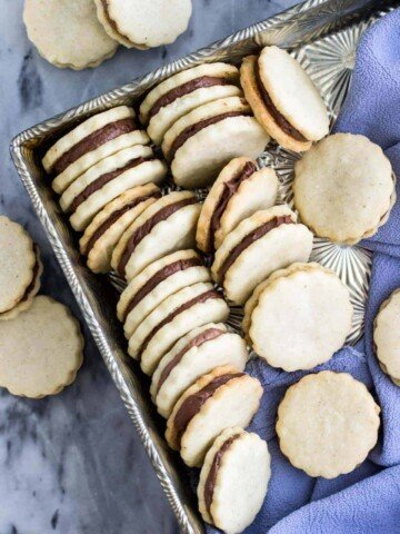 Vanilla and chocolate sandwich cookies, lined up in a silver serving tray