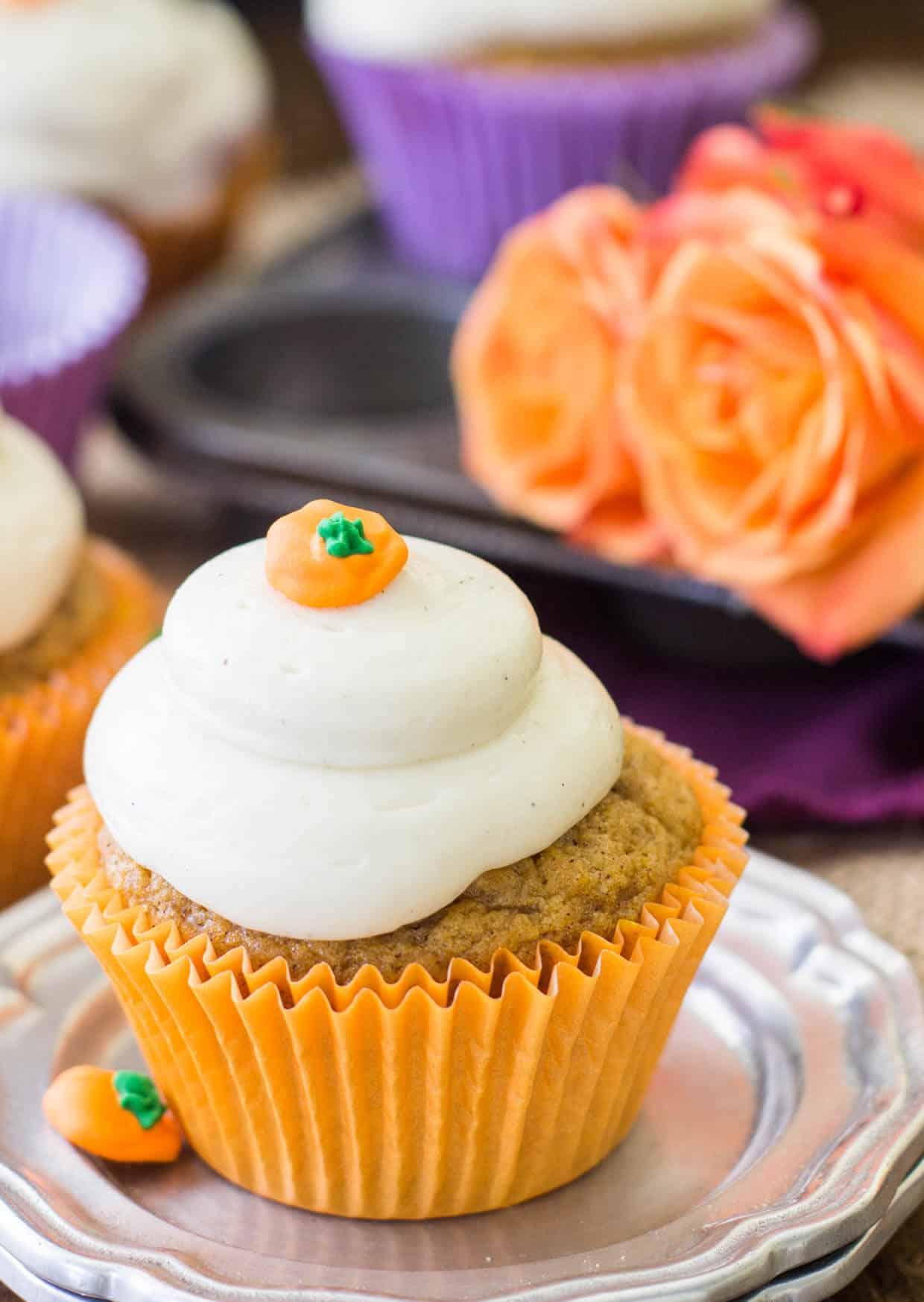 Pumpkin cupcake in orange wrapper on silver plate
