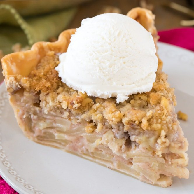slice of apple pie with ice cream on white plate