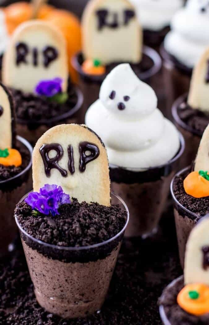 Ghosts in the graveyard dessert shooters, topped with mini tombstones, mini pumpkins, and ghoulish figures
