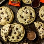Overhead of Peanut butter cup stuffed chocolate chip cookies on a baking sheet, surrounded by reeses peanut butter cups
