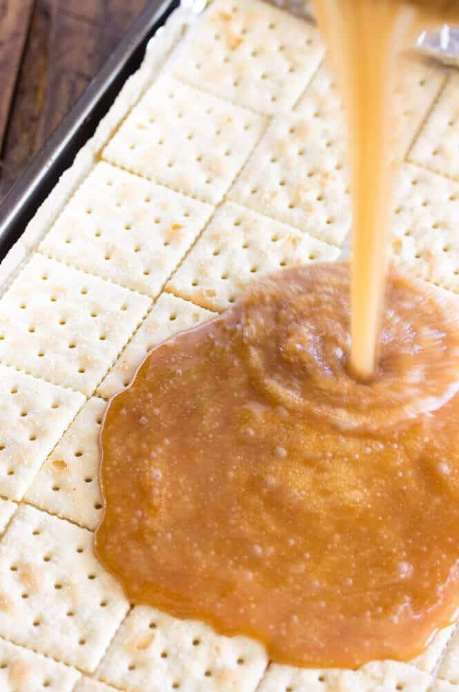 Caramel sauce poured onto saltine crackers in baking sheet