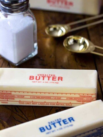 Stick of salted butter, unsalted butter, and a shaker of salt