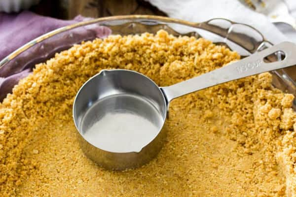 A homemade graham cracker crust in process -- flattening the crust using a measuring cup