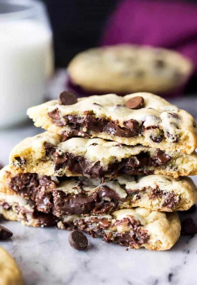 A stack of fudge filled chocolate chip cookies with melty fudge-filled centers