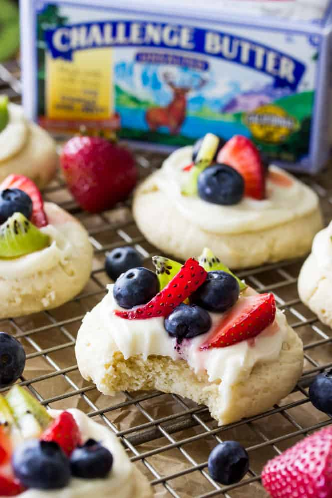 Sugar cookies topped with frosting and sliced fruit (blueberries, kiwi, and strawberry)