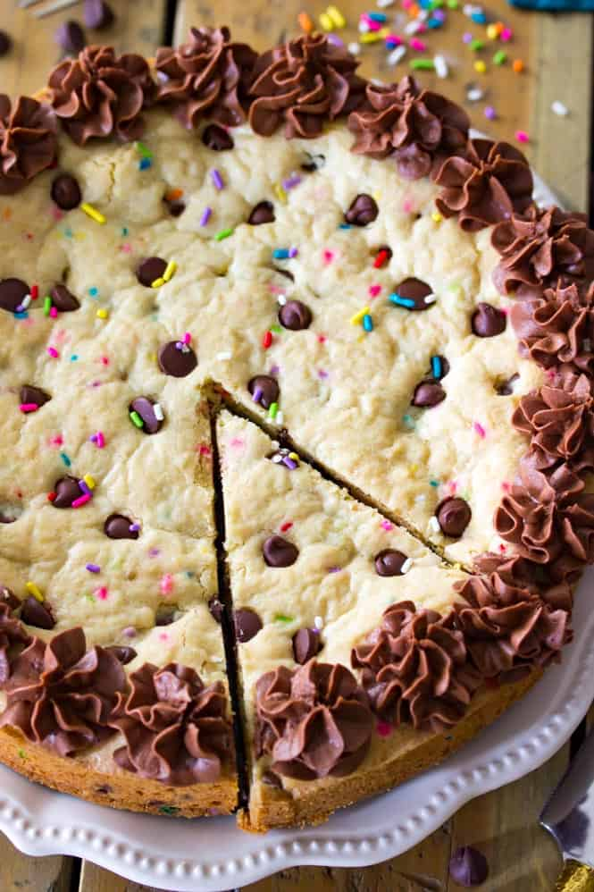A giant soft baked chocolate chip cookie cake! Complete with sprinkles and chocolate frosting! || Sugar Spun Run