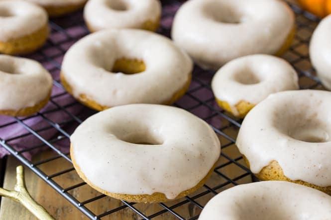Glazed pumpkin spice donuts on cooling rack