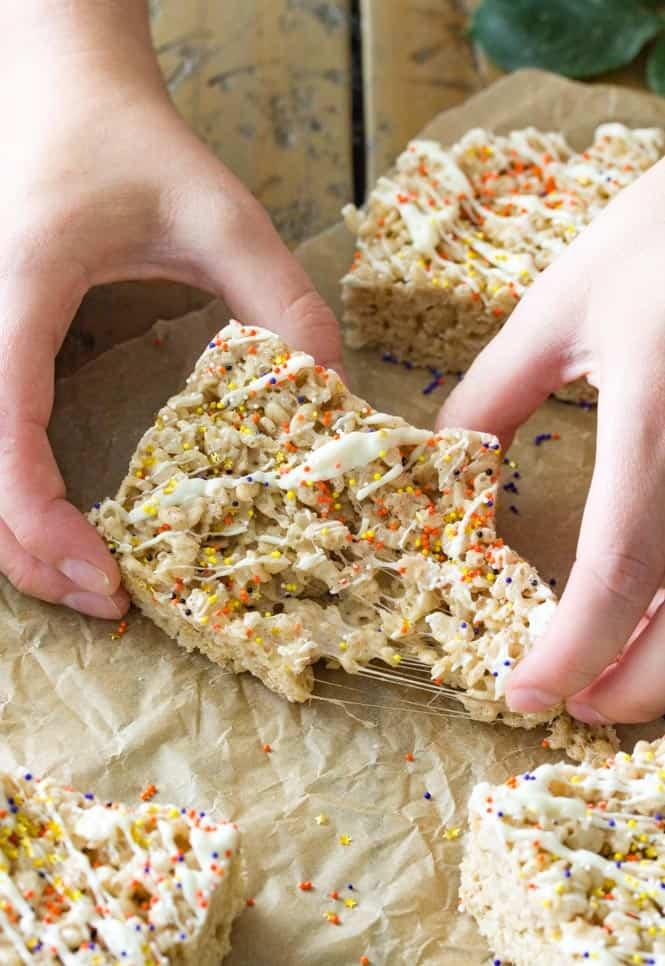 Hand pulling apart pumpkin spice rice krispie treats