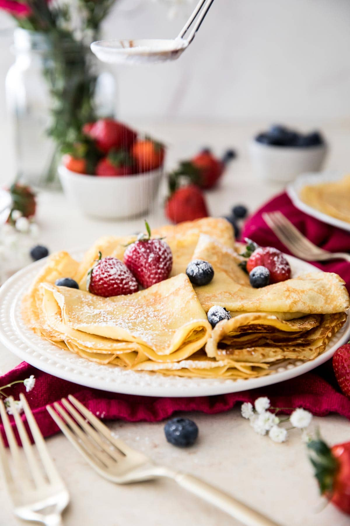 folded up crepes on white plate topped with fruit