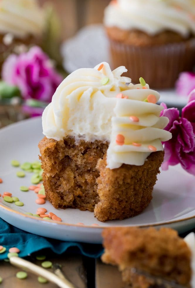 Bite taken out of a carrot cake cupcake with cream cheese frosting