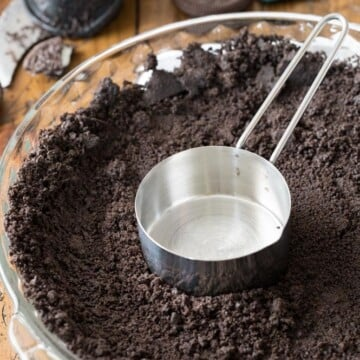 Measuring cup pressing oreo cookie crumbs into bottom of pie plate