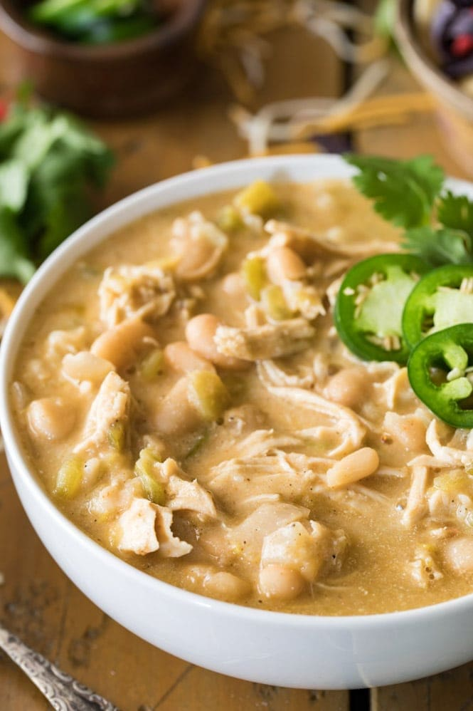 A bowl of white chicken chili topped with jalapeno slices