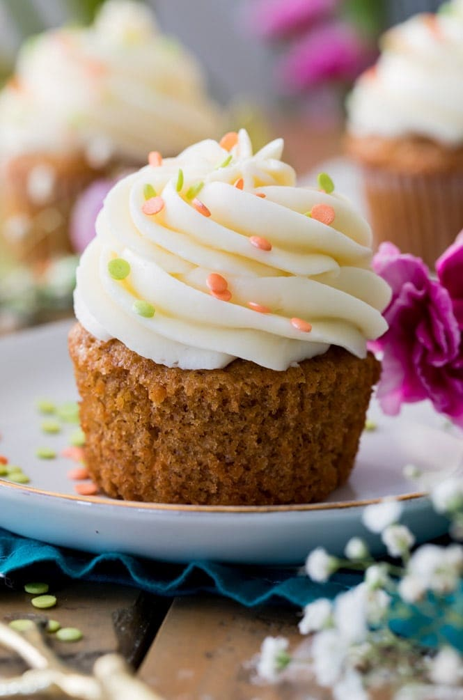 Carrot cake cupcake without wrapper on white plate topped with cream cheese frosting and orange sprinkles