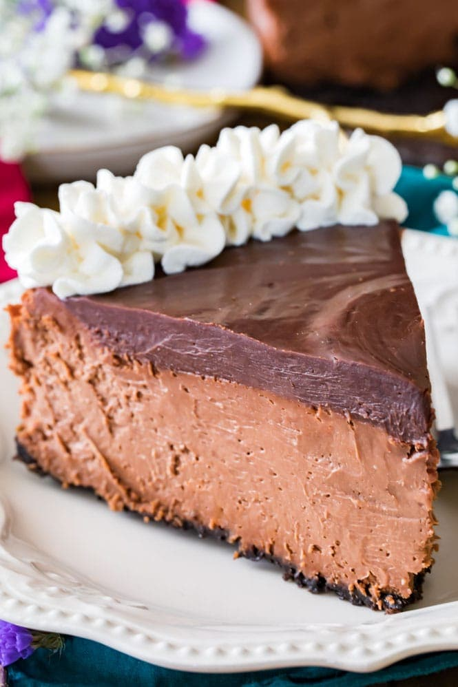 A slice of chocolate cheesecake topped with chocolate ganache and whipped cream