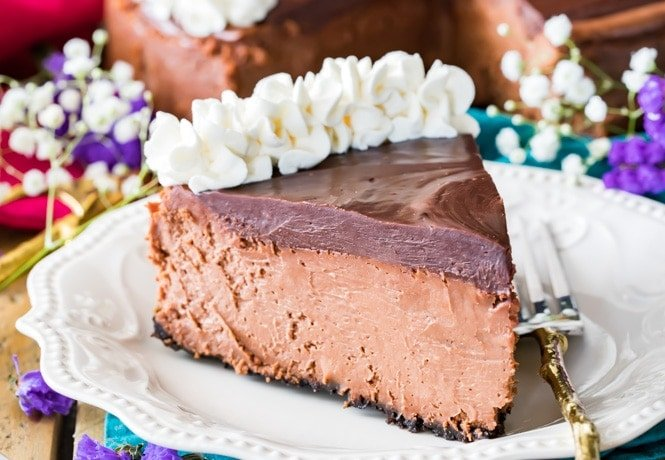 A slice of chocolate cheesecake surrounded by flowers