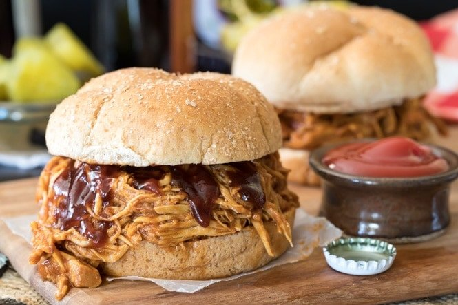 BBQ Pulled Chicken sandwich on a wooden platter beside a ketchup dish