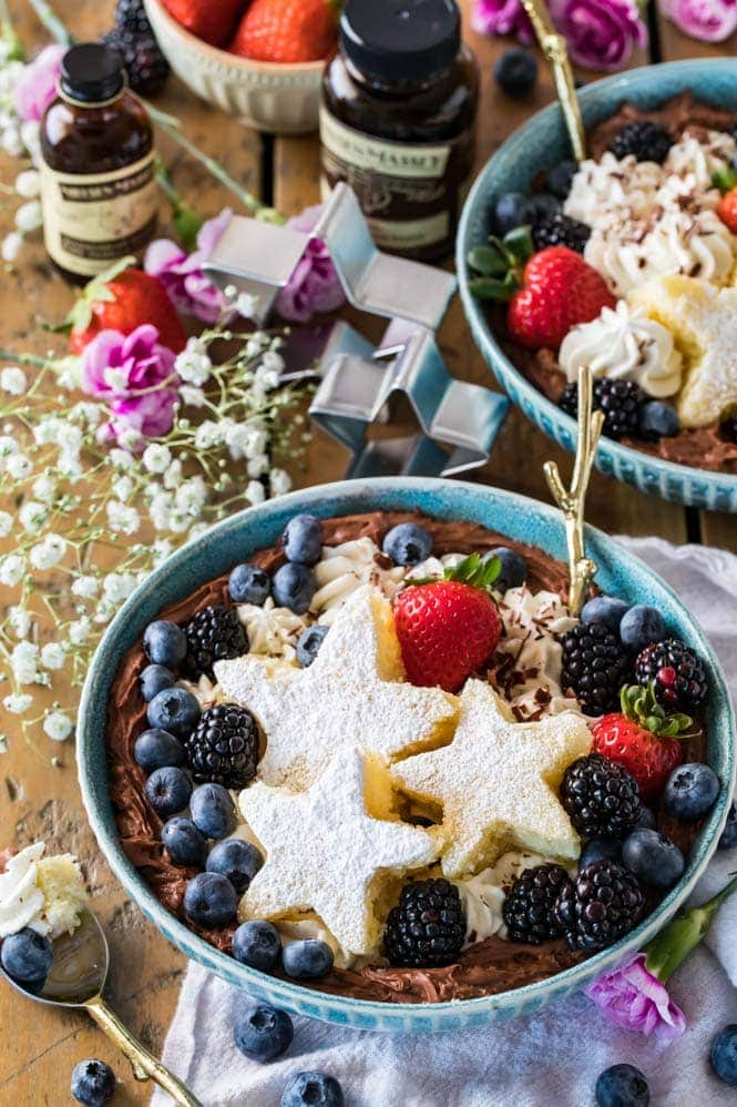 A dessert bowl decorated with star-shaped cake slices and fruit
