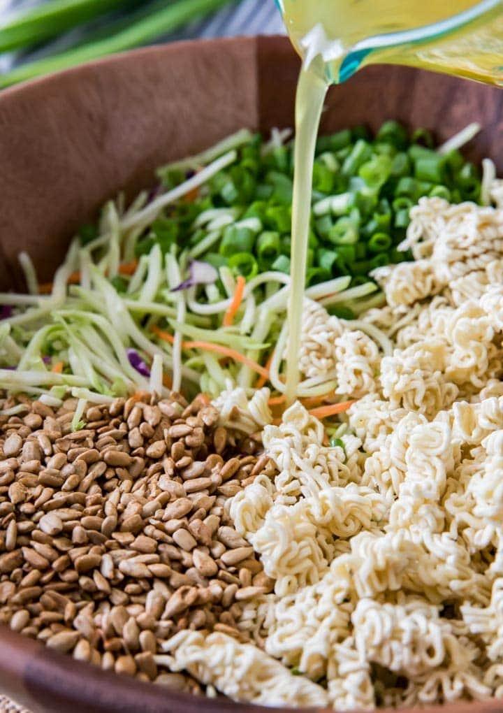 Pouring salad dressing over ramen noodle salad