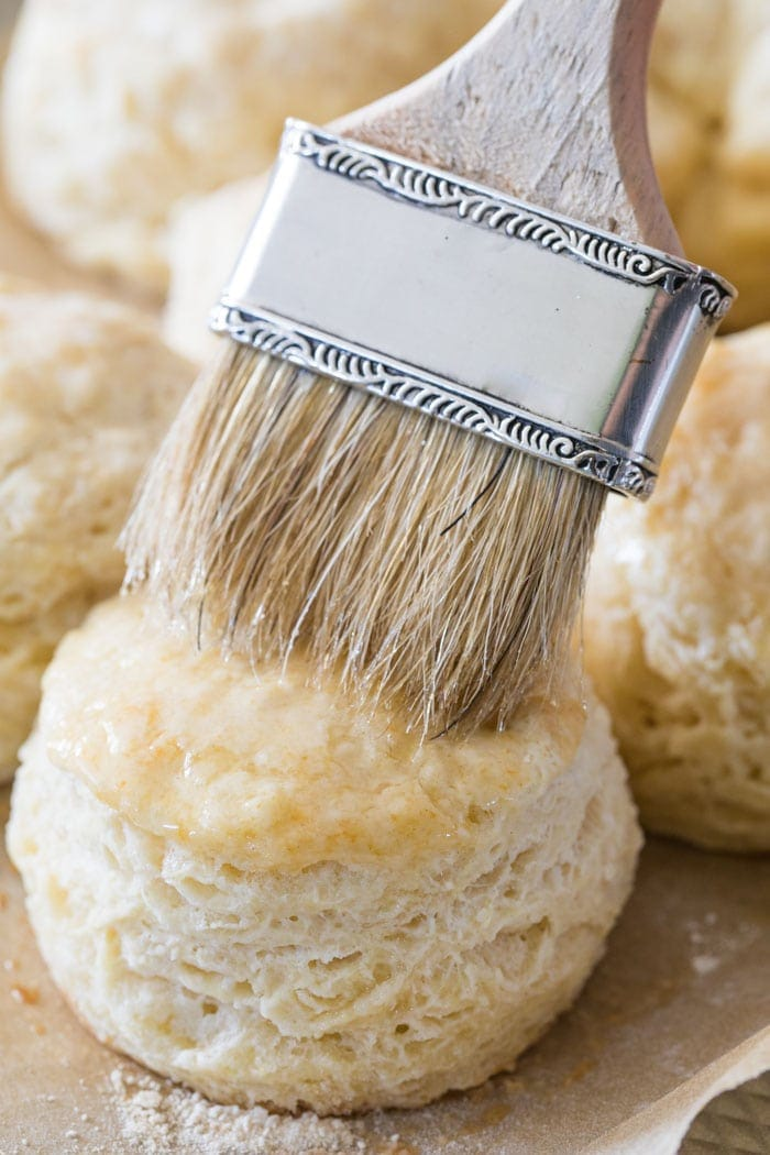 Brushing melted butter on a freshly baked homemade biscuit