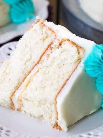 Slice of white cake with white icing and blue icing decorations on plate
