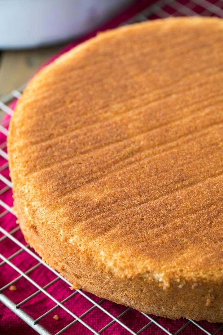 The golden brown exterior of a cooling white cake