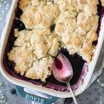 freshly baked cobbler with spoon in blueberry juices