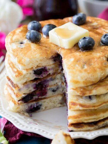 Stack of blueberry pancakes topped with pat of butter