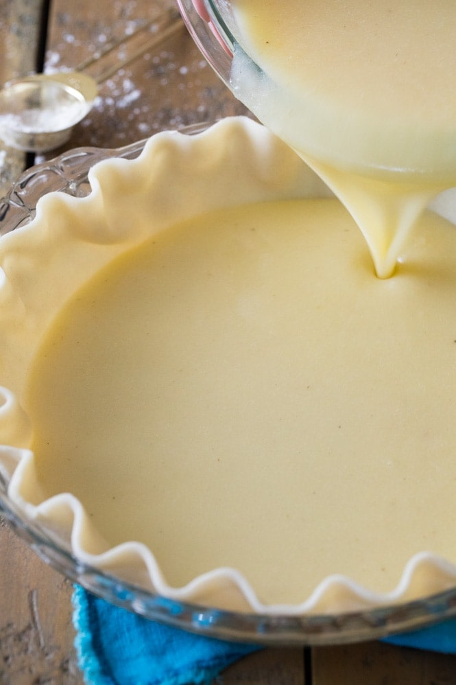 Pouring buttermilk pie filling into pie shell