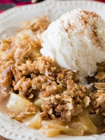 Apple crisp with ice cream on white plate