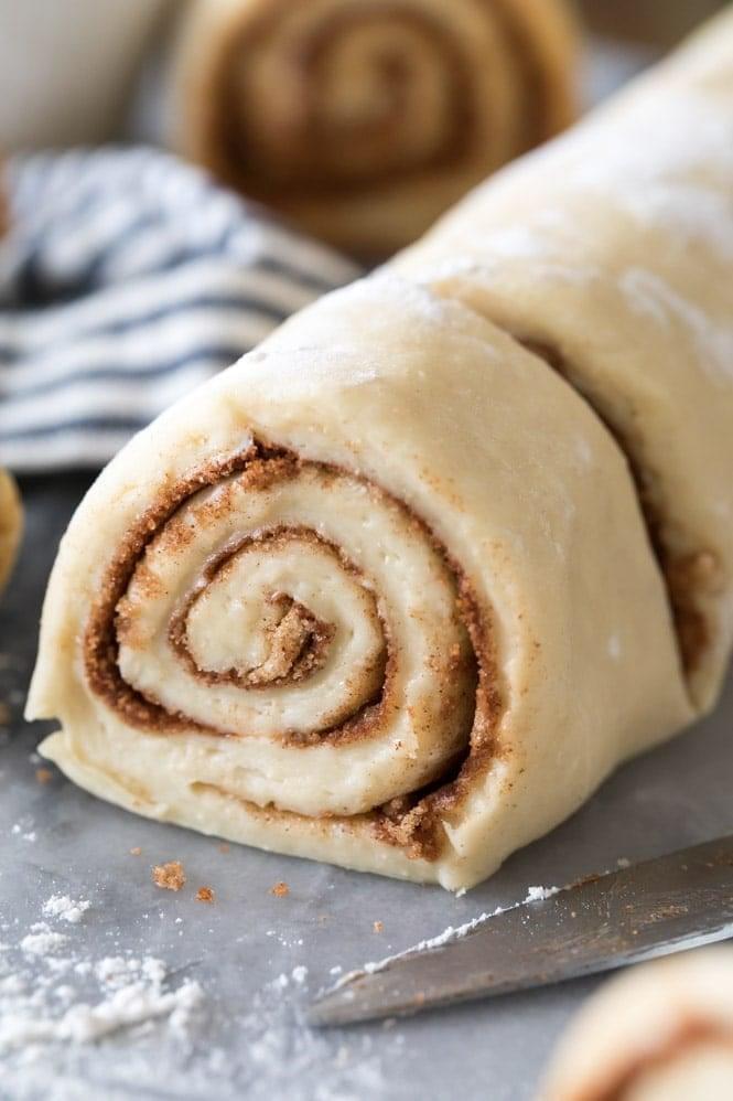 slicing cinnamon roll dough log