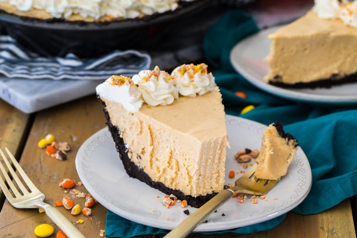 slice of peanut butter pie on white plate with forkfull