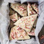 Peppermint Bark pieces in container on marble surface